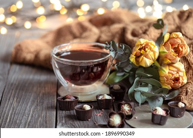 Festive still life with a drink in a cup, chocolates and flowers on a blurred background with bokeh.