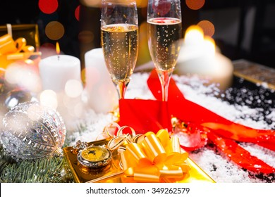 Festive Still Life - Pocket Watch on top of Gold Wrapped Gift in Still Life with Champagne Glasses, Lit Candles and Glittering Christmas Decorations