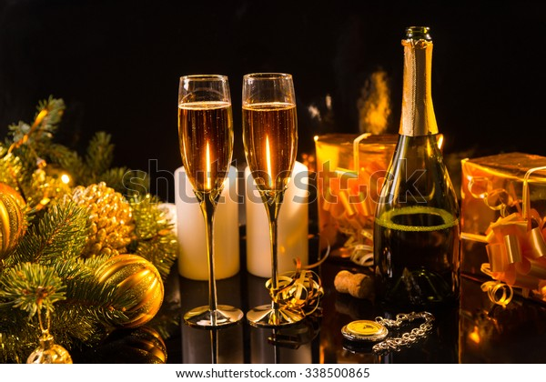 Festive Still Life - Two Glasses of Sparkling Champagne with Bottle, Candles, Gifts, Pocket Watch and Christmas Decorations on Black Background in Warm Lighting