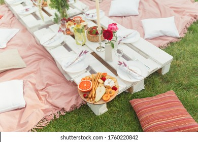 Festive summer picnic with delicious snacks, fruits and wine, decorated with beautiful flowers and candles in pink colors for hen party. Good food serving on white pallet table. Selective focus