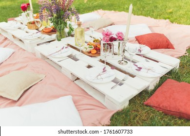 Festive summer picnic in the garden with tasty food, white wine and beautiful flowers. Birthday or wedding celebration. Hen-party. Leisure and rest. White pallet table and pillows for seating