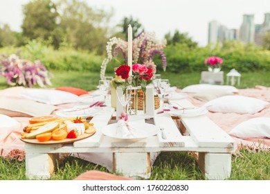 Festive summer picnic with tasty snacks, fruits and wine, decorated with beautiful flowers and candles in pink colors for hen-party. Good food serving. Event agency. Selective focus