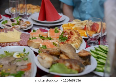 A festive table in the center of which stands a plate of sandwiches with red fish and parsley