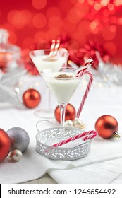 festive table with christmas drinks and red and silver decorations. Red and white straws and candy canes. room for text