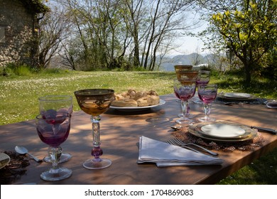 Festive table with crystal chalices, porcelain plates and silverware, in the countryside under the shade of a tree. Typical neapolitan baked bread called Casatiello on the table.
