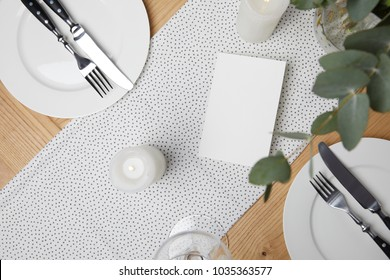 Festive Table With Cutlery On Plates On Table With Candles