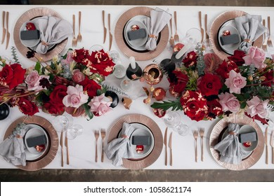 Festive table decor. With different natural colors and flowers. Luxury wedding, party, birthday. View from above. Red, pink, cooper, golden. Candles.