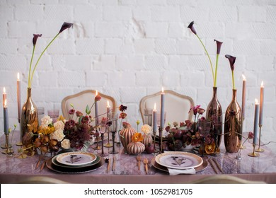 Festive table decor. Golden cutlery. With different natural colors and flowers. Garnet. Luxury wedding, party, birthday. View from above. Violet, pink. Candles