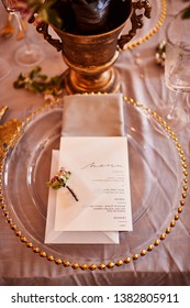 Festive table decor. Golden cutlery. With different natural colors and flowers. Garnet. Luxury wedding, party, birthday. View from above. Gold, pink. Candles