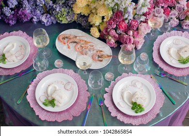 Festive table decor. Luxury wedding, party, birthday. View from above. Different seafood. White wine, prawns, fish. multicolored, Pink Lavender, Arcadia, Ultra Violet. flowers, carnations, roses.