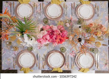 Festive table decor. Pastel colors. Luxury wedding, party, birthday. Yellow berries. Copper chairs and dishes, gold and silver cutlery. Chinese, European, chinoiserie style. Peonies, roses. View above