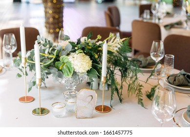 Festive table decor. Stylish stone tablet with table number in gray, green branches and peonies, candles in gold candlesticks