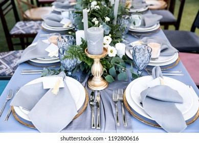 Festive table decorated with garland of branches and flowers on the center, candles, silverware and plates with silk napkins on dusty blue tablecloth