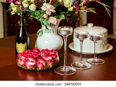 Festive table decorated with a vase of flowers, lighted candlesticks and a bottle of champagne. Homeliness in the interior before Christmas