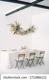 festive table with a floral bouquet, candles, chairs and a flower garland