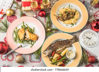Festive table - food in plates, drinks in glasses. Christmas and New Year. Healthy fresh food - fish, meat, vegetables. Close-up view from above.