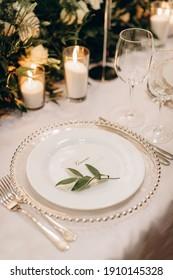 mesa festiva de los recién casados, plato con tarjeta de visita del novio y ramas de olivo en una mesa con copas de vino y flores. Mesa de un día de boda, celebración de bodas.