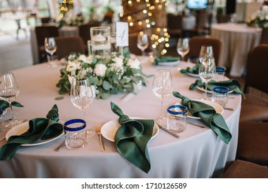 Festive table on wedding banquet decorated by napkins and composition of flowers. Reception