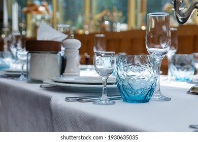 Festive table set, catering with white cloth, plates, forks, blue glasses, salt and pepper pots for wedding, family event or happy birthday party.