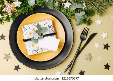 Festive table setting. Black Plates with gift and Christmas decorations with fir-tree branch. Flat lay, top view.