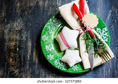 Festive table setting for Christmas eve in rustic style on dark wooden background