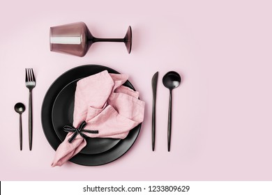 Festive table setting with cutlery, pale pink napkin, black plates and wine glass on pastel background. Flat lay, top view