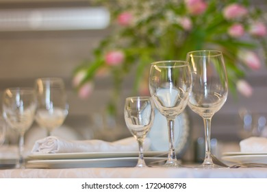 Festive table setting. Empty glasses and plates outdoors. Banquet on the terrace. Restaurant in the nature. Table setting.