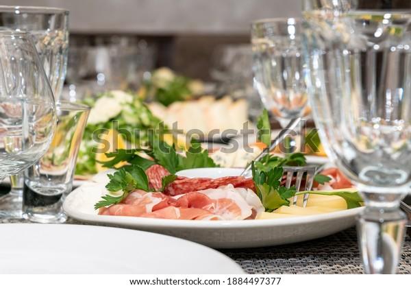 Festive table setting, family dinner with served italian antipasti - marinated salmon, hamon, Carpaccio, pear, basil. Tablescape