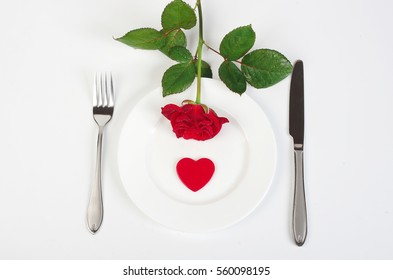 A festive table setting. Plate with red rose and red heart, knife, fork on a white tablecloth