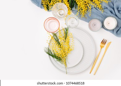 Festive table setting. Plates and cutlery with gray decorative textile and yellow flowers on white background. Beautiful arrangement.