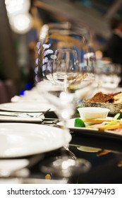 Festive table setting in a restaurant or cafe. Event and celebration. Details and closeup of clean transparent wine glasses. Catering. Festive party in a nightclub. Soft selective focus.