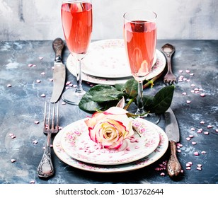 Festive table setting for valentines day, plates and glasses with pink champagne for couple of lovers, gray background, selective focus