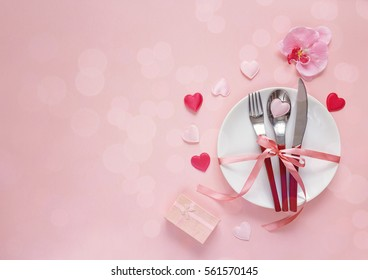Festive table setting for Valentine's Day with cutlery, orchid, gift box and hearts on pink  table. Space for text. Top view.