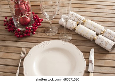 Festive table setting of white plate, cutlery, vine glasses with red berries decorations and wrapped candies over wooden outdoors table surface