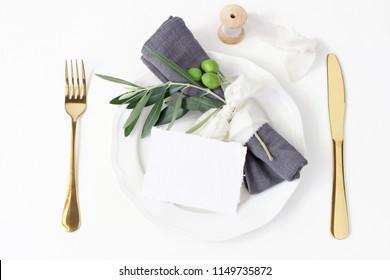Festive table summer setting. Golden cutlery, olive branch, linen napkin, porcelain dinner plate and  silk ribbon on white table background. Blank card mockup. Mediterranean wedding, restaurant.