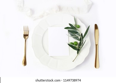 Festive table summer setting with golden cutlery, olive branch, porcelain plate and  silk ribbon. Blank card mockup. Mediterranean wedding or restaurant menu concept. Flat lay, top view.