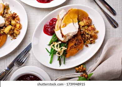 Festive Thanksgiving dinner table with plates of food, turkey and all the sides