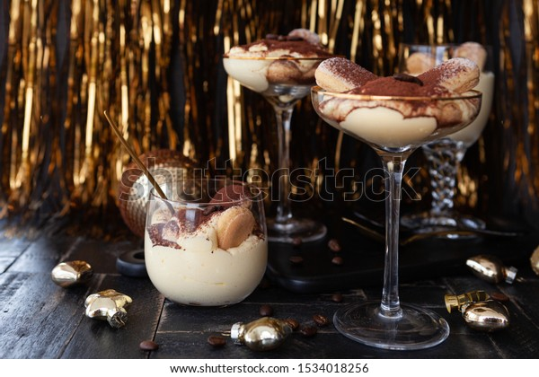 Festive tiramisu dessert in glasses with golden decorations for the holidays