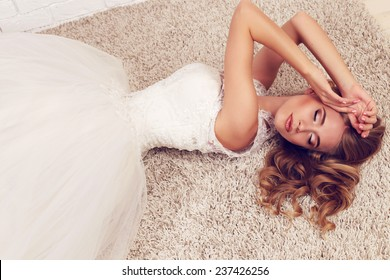 festive wedding photo of chic sexy bride in white evening lace dress like a princess, with blond beautiful curly hair, lying and relaxing on the carpet