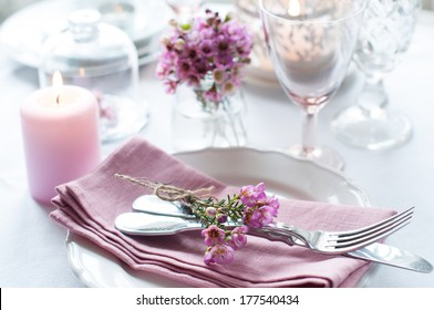 Festive wedding table setting with pink flowers, napkins, vintage cutlery, glasses and candles, bright summer table decor.