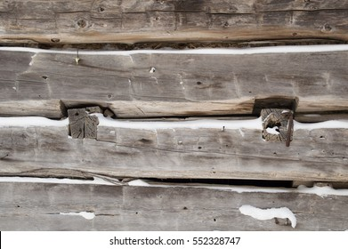 A festive winter background with weathered silvery grey horizontal sawn logs with snow in between.