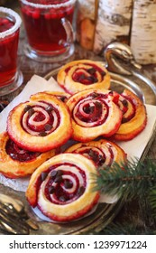 Festive winter pastries.  Sweet cranberry roll buns with chocolate drops and two cups of cranberry fruit drink. Focus selective
