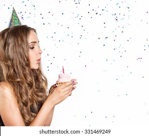 Festive woman with cake blow out the candles on a background of confetti