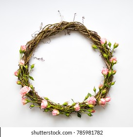 Festive wreath of grape vines with decorative roses, leaves. Wedding, birthday, Valentine's day concept. Beautiful DIY natural wreath on white background. Flat lay, top view