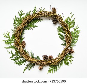 Festive wreath of grape vines with thuja branches and cones. Natural DIY wreath. Christmas or any other holiday decorative wreath on white background. Flat lay, top view