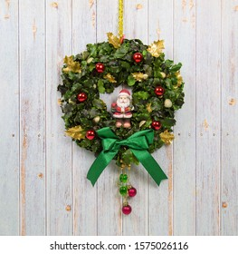 Festive wreath green with Santa Claus in the center, spruce branches, suspended on the background of light lilac wooden fence. Christmas, Toys, New year, decorations.