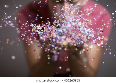 Festive young man throwing confetti