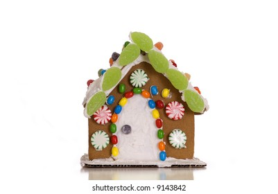 A festively decorated gingerbread house isolated against a white background.