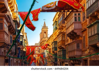 Festively decorated street with banners for St Augustine Feast in the old town of Valletta, Malta