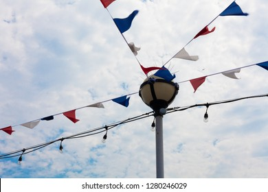 Festivity Flag and Stringed Bulbs Hanging Horizontally from Lamp Post. Different Color Banner for Attraction. Decoration Ideas in Celebrating an Occasion.